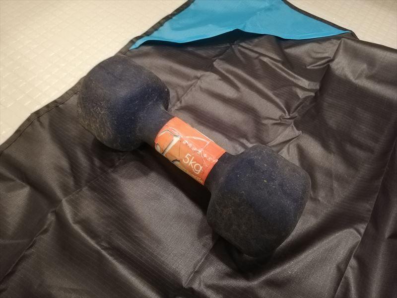 濡れた床の上にレジャーシートを敷き、15kgのダンベルを